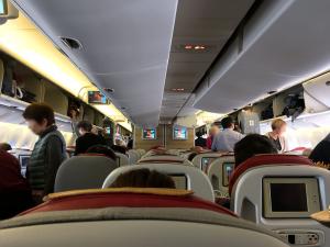 アリタリア航空の機内。座席の上から少し赤色で見えているのが不必要な枕